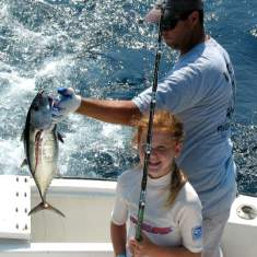 Young lady watches first mate holding her tuna caught on an offshore charter.